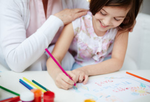 Little girl making card for her mom with her grandmother near by